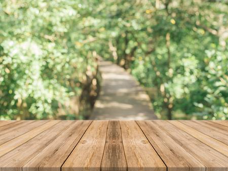 Tavola di legno tavolo vuoto di fronte a sfondo sfocato. Prospettiva di legno marrone sopra gli alberi di sfocatura nella foresta - può essere usato mock up per la visualizzazione o il montaggio i vostri prodotti. stagione primaverile. epoca filtrata.