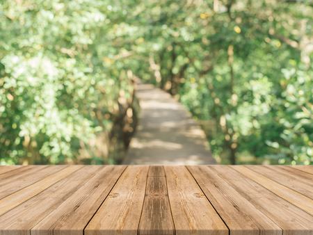 wooden planks: Wooden board empty table in front of blurred background. Perspective brown wood over blur trees in forest - can be used mock up for display or montage your products. spring season. vintage filtered.