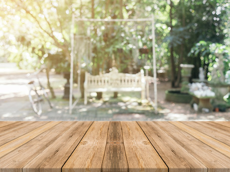 forest products: Wooden board empty table in front of blurred background. Perspective brown wood over blur trees in forest - can be used mock up for display or montage your products. spring season. vintage filtered.