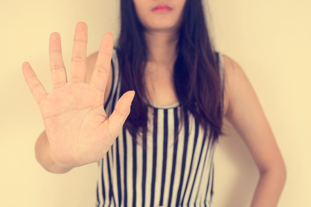 restrain: Young woman showing her denial with NO on her hand, vintage filtered image.