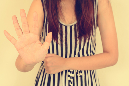 denial: Young woman showing her denial with NO on her hand, Vintage filtered image. Stock Photo