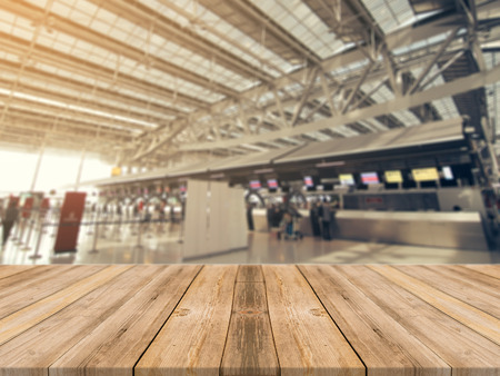 Empty wood table top with airport departure abstract blur background with bokeh light,Mock up for display or montage of product,Business presentation