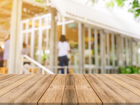 tablero de mesa vacía de madera delante de fondo borroso. Perspectiva de madera marrón sobre la falta de definición en la cafetería - se puede utilizar para la visualización o Montage su products.Mock para la exhibición de productos.