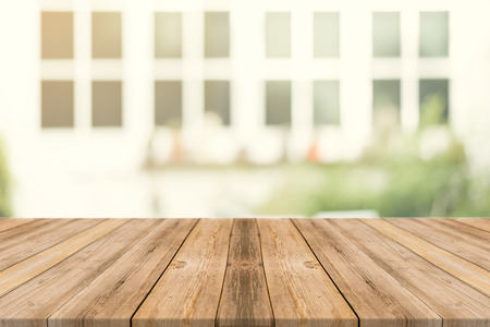 Wooden board empty table in front of blurred background. Perspective brown wood over blur in coffee shop - can be used for display or montage mock up your products. vintage filtered image.