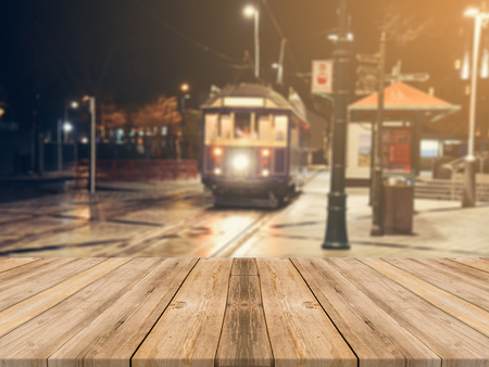 display advertising: Wooden board empty table top on of blurred background. Perspective brown wood table over blur in street city night background