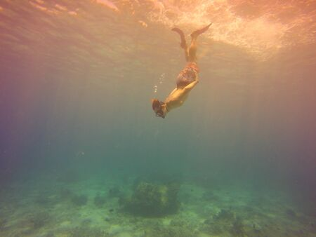 Underwater selfie shot with young man diving on a breath hold in a tropical sea over sandy bottom. Deep blue sea. Wide angle shot. Vintage filtered image.