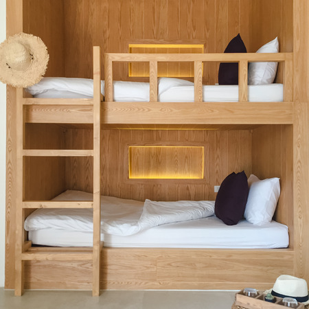 twin bed: Clean hostel room with wooden bunk beds.