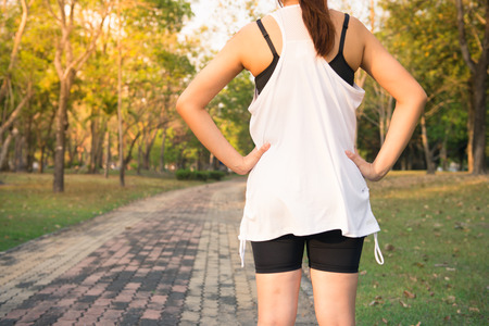 Back view of young fitness woman running on the road in the morning, People and sport concept, Selective focus, Vintage effect style pictures. Stock Photo