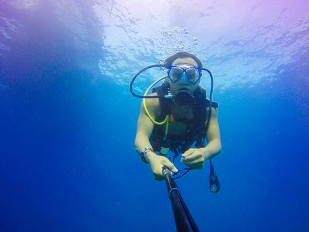 scuba goggles: Underwater scuba diving selfie shot with selfie stick. Deep blue sea. Wide angle shot.