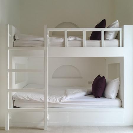 木製の二段ベッドと清潔なホテルの部屋。ビンテージ効果のスタイルの写真。