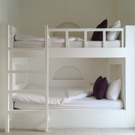 Clean hotel room with wooden bunk beds. Vintage effect style pictures. Фото со стока - 72483104