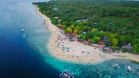 Aerial view of sandy beach with tourists swimming in beautiful clear sea water of the Sumilon island beach landing near Oslob, Cebu, Philippines. - Boost up color Processing.