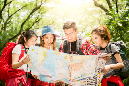 Hiking - hikers looking at map. Couple or friends navigating together smiling happy during camping travel hike outdoors in forest. Young mixed race Asian woman and man. Foto de archivo