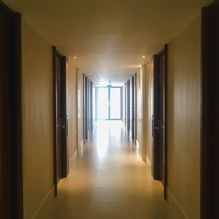 Corridor with lots of dark brown doors. White walls and ceiling, concrete floor. Concept of hotel lobby.