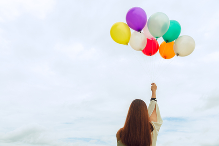 Woman lifestyle concept - woman hand holding a bunch of colored balloons with blue sky. Vintage tone filter color style.