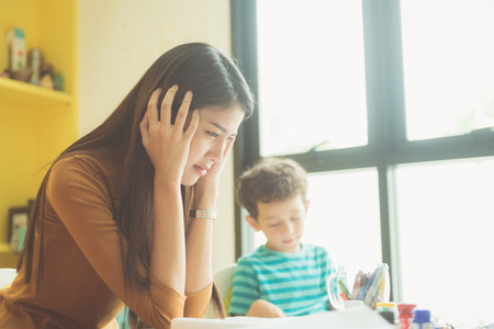 tired: Asian teacher kindergarten hands closed both ears of her in an upset of failed to quell quited naughty, of the boys in class at preschool kids argument. Vintage effect style pictures.