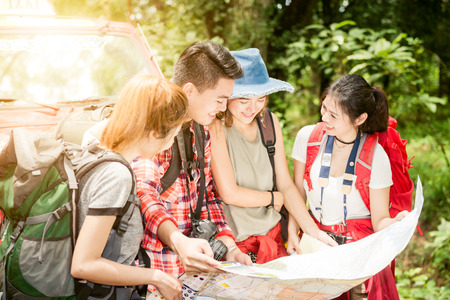 Hiking - hikers looking at map. Couple or friends navigating together smiling happy during camping travel hike outdoors in forest. Young mixed race asian woman and man. Hiking travel concept. Stock Photo