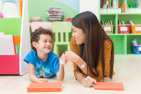 Young asian woman teacher teaching american kid in kindergarten classroom with happiness and relaxation. Education, elementary school, learning and people concept - teacher help school kids classroom. Stock Photo - 89402347