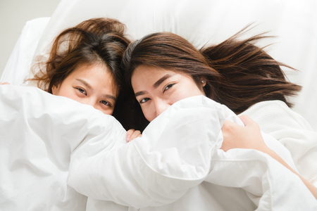 Top view of beautiful young asian women lesbian happy couple showing surprise and looking at camera while lying in bed under blanket. Funny women after wake up. Lesbian couple together indoors concept Archivio Fotografico