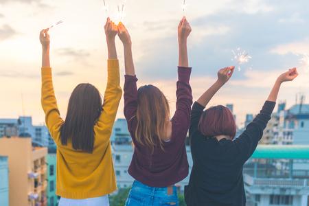 Openluchtschot van jonge mensen bij dakpartij. De gelukkige groep vrienden van het Aziëmeisje geniet van en speelt sterretje bij dak hoogste partij bij avondzonsondergang. Feestelijke viering feestelijke partij. Teenage lifestyle-feest. Stockfoto