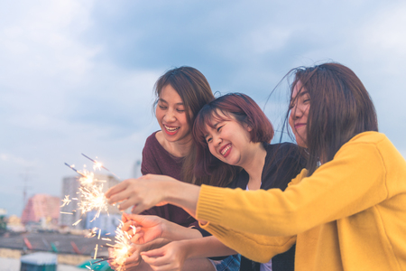 Outdoor shot of young people at rooftop party. Happy group of asia girl friends enjoy and play sparkler at roof top party at evening sunset. Holiday celebration festive party. Teenage lifestyle party. Stock Photo