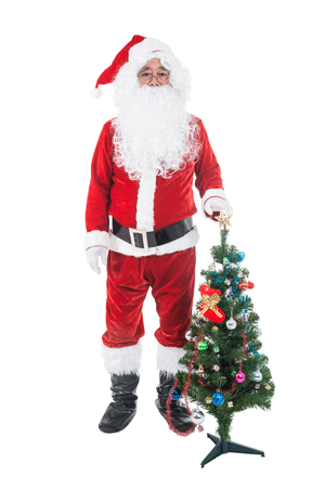 Christmas theme - Santa Claus holding christmas tree and his bag full of gifts over white background. Santa Claus christmas concept. Stock Photo