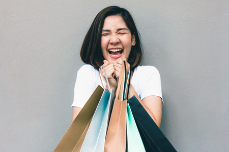 Joven mujer asiática de compras de verano feliz con bolsas de compras sobre fondo gris en el espacio de la copia
