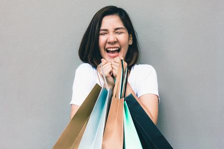 Junge glückliche sommerliche einkaufende asiatische Frau mit Einkaufstaschen auf grauem Hintergrund am Kopienraum