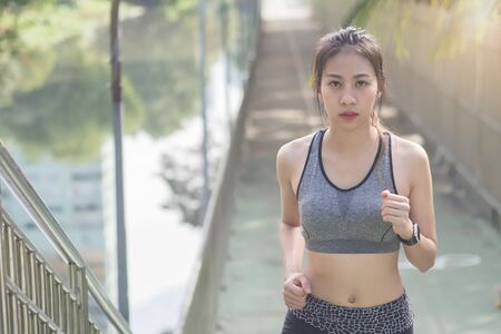 Young asian woman running on sidewalk in morning. Health conscious concept with copy space. Young sport asian woman running upstairs on city stairs. Fitness sport people and healthy lifestyle concept. Standard-Bild