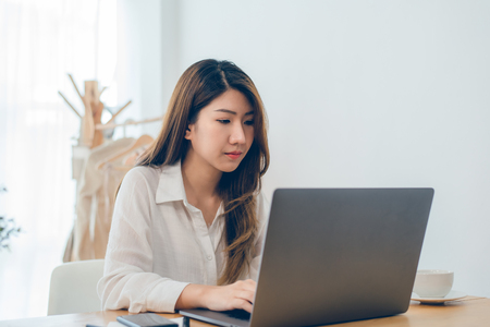 Beautiful young smiling Asian woman working on laptop while at home in office work space. Businesswoman working from home via portable computer writing on keyboard. Enjoying time at home.