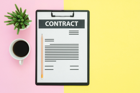 Flat lay design of office desk working space  - Top view of a contract document and coffee cup decorated with small cactus on pink yellow pastel color with copy space. Pastel working space background.