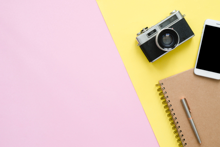 Flat lay design of travel summer concept - Top view of brown notebook, pencil, tablet and camera on pink and yellow pastel color screen with a copy space. travel summer on pastel color background.