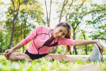 Healthy young asian woman exercising at park. Fit young woman doing training workout in morning. Young happy asian woman stretching at the park after a running workout. Exercise outdoor concept.