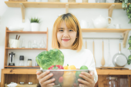 Smiling asian beautiful woman sitting in the kitchen at home and holding a salad bowl. Young happy female eating healthy salad with green fresh ingredients for healthy body.