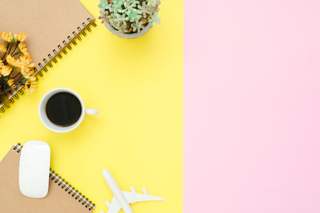 Flat lay design of travel summer concept - Top view of notebook, airplane, little tree, flower, coffee and wireless mouse on pink and yellow pastel color copy space. travel on pastel color background. Stock Photo