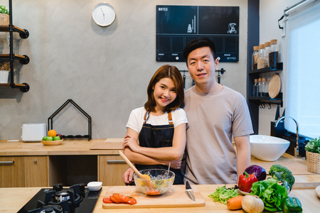 Asian couple prepare food together. Beautiful happy asian man and woman are cooking in the kitchen. Young asian couple have romantic time while staying at home. Couple lifestyle at home concept.