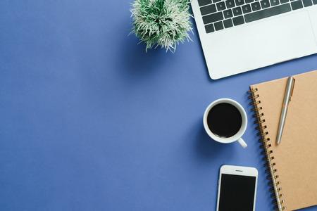 Espace de travail de bureau - photo maquette vue de dessus plat laïque de l'espace de travail avec ordinateur portable, smartphone, café et ordinateur portable sur fond bleu pastel. Concept de bureau de travail de fond de couleur bleu pastel