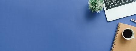 Minimaler Arbeitsbereich - Kreatives Flachbild des Arbeitsbereichsschreibtisches. Draufsicht-Schreibtisch mit Laptop, Notizbüchern und Kaffeetasse auf blauem Hintergrund. Panorama-Bannerhintergrund mit Kopierraum.