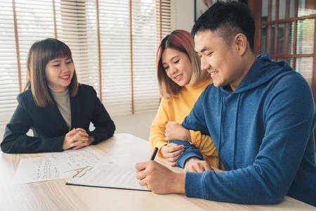 Szczęśliwa młoda azjatycka para i agent nieruchomości. Wesoły młody człowiek podpisywania niektórych dokumentów siedząc przy biurku wraz z żoną. Zakup nowej nieruchomości mieszkalnej. Podpisanie umowy w dobrym stanie. Zdjęcie Seryjne
