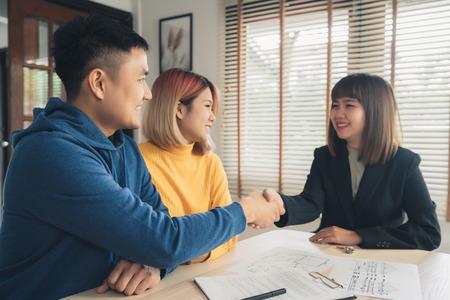 Feliz pareja asiática joven y agente de bienes raíces. Hombre joven alegre que firma algunos documentos y apretón de manos con el corredor mientras está sentado en el escritorio. Firma de contrato en buen estado. Foto de archivo