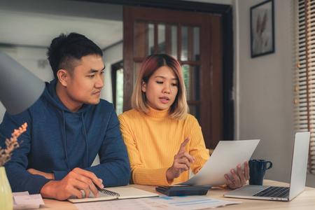 Junges asiatisches Paar, das Finanzen verwaltet und ihre Bankkonten mit Laptop und Taschenrechner am modernen Haus überprüft. Frau und Mann erledigen gemeinsam Papierkram und zahlen online Steuern auf dem Notebook-PC.