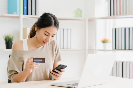 Hermosa mujer asiática con smartphone comprando compras en línea con tarjeta de crédito mientras usa suéter sentado en el escritorio en la sala de estar en casa. Mujer de estilo de vida en el concepto de hogar.