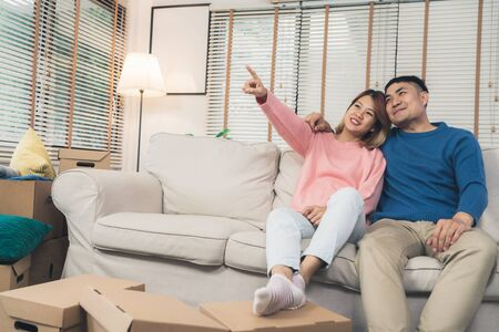 Sweet happy young Asian couple moving clothes and many objects from old home to their new home and relax on sofa in living room at their home. Lifestyle couple move new home. Archivio Fotografico - 129682375