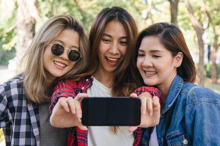 Gruppe asiatischer Frauen mit Smartphone unter Selfie während der Reise im Park in der Stadt in Bangkok, Thailand. Lifestyle schöne Freunde touristischen Reiseurlaub in Thailand Konzept.
