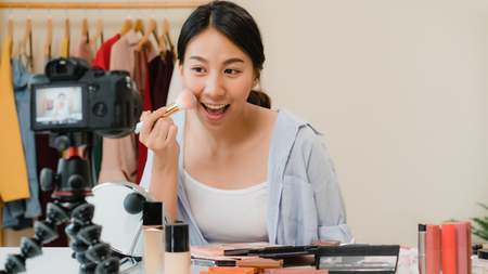 Beauty blogger present beauty cosmetics sitting in front camera for recording video. Beautiful asian woman use cosmetics review make up tutorial broadcast live video to social network by internet.