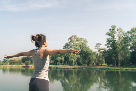 Young asian woman yoga outdoors keep calm and meditates while practicing yoga to explore the inner peace. Yoga have good benefits for health near lake at park. Sport and Healthy lifestyle concept. Stock fotó