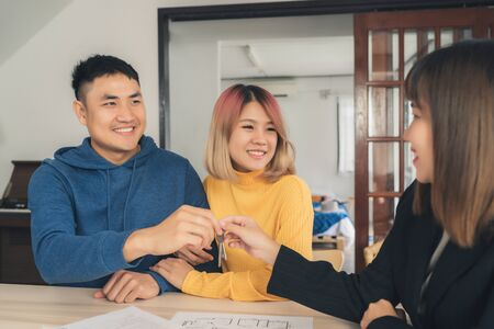 Happy young Asian couple and realtor agent. Cheerful young man signing some documents and handshaking with broker while sitting at desk. Signing good condition contract.
