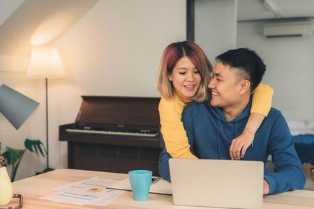 Young asian couple managing finances, reviewing their bank accounts using laptop computer and calculator at modern home. Woman and man doing paperwork together, paying taxes online on notebook pc. Archivio Fotografico - 129684575