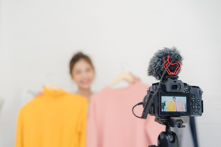 Asian fashion female blogger online influencer holding shopping bags and lots of clothes on clothes rack for recording new fashion video broadcast live video to social network by internet at home.