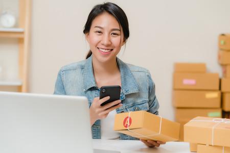 Hermosa mujer de negocios joven empresaria asiática inteligente propietaria de una PYME que controla el producto en el código qr de escaneo de existencias trabajando en casa. Propietario de una pequeña empresa en el concepto de oficina en casa. Foto de archivo